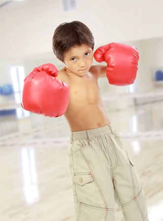boy boxing: portrait of happy young kid with boxing glove ready to fight in the gym Stock Photo