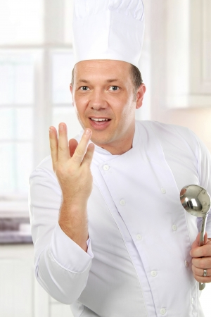 culinary skills: Smiling chef cooking something in the kitchen