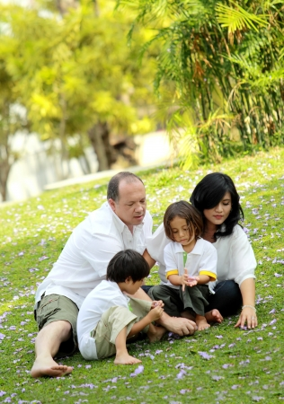 candid: Portrait of happy asian caucasian family in the park Stock Photo