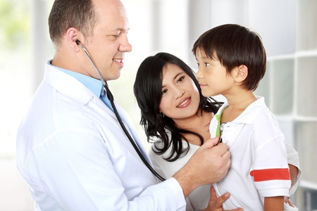 doctor stress: Portrait of a doctor examining youthful patient with stethoscope