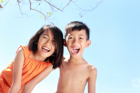 Portrait of happy asian kids having fun in beautiful sunny day photo
