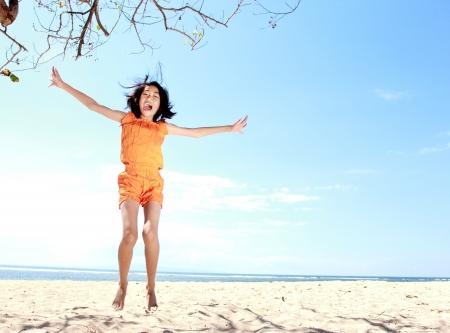 little asian girl jumping and having fun in the beach 版權商用圖片