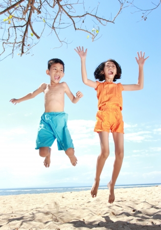 Portrait of happy asian kids in the beach jumping together photo