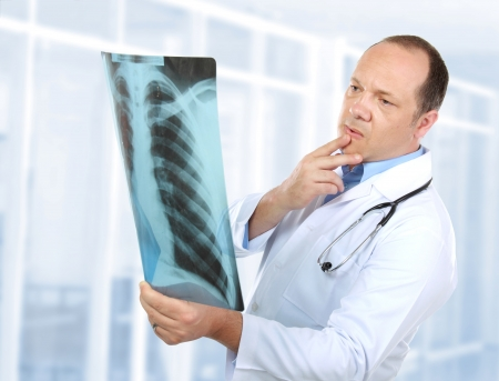 portrait of curious doctor looking at x-ray in the laboratory photo