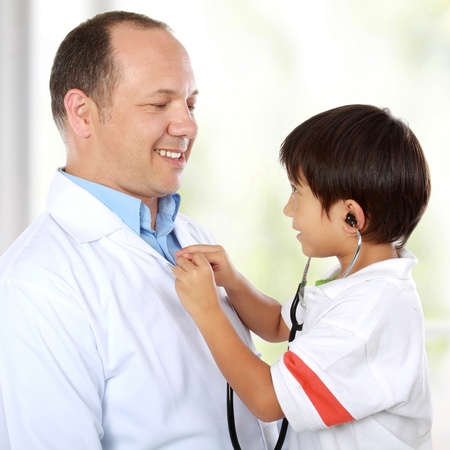 Portrait of a doctor having fun using stethoscope with his young kid patient photo