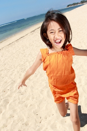 Portrait of pretty little girl running in the beach Stock Photo - 15047144