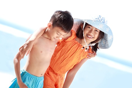 Portrait of happy asian kids having fun in beautiful sunny day in the beach photo