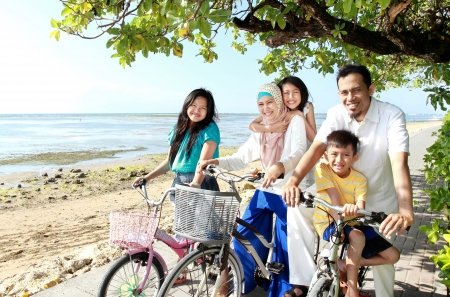 Happy asian family riding bikes in the beautiful morning at the beach photo