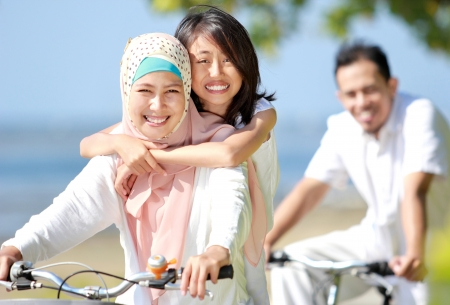 moslem: Happy muslim family riding bikes together in beautiful sunny day Stock Photo