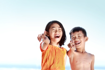 Portrait of happy asian kids pointing to the camera having fun photo