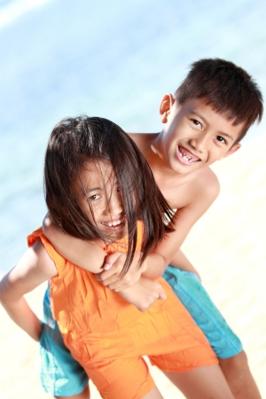 Portrait of a happy little girl carrying her brother in the beach photo