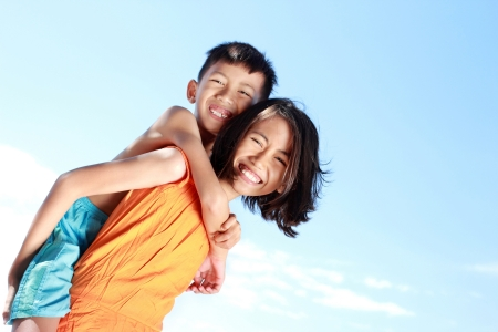 asian family outdoor: Portrait of a happy kids having fun doing piggyback ride