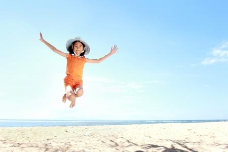 ジャンプとビーチで楽しい小さなアジアの女の子