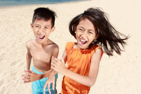Portrait of happy little boy and girl running in the beach together photo