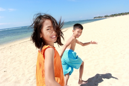 asian family outdoor: kids having fun running together in the beach Stock Photo