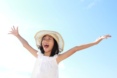 yell: Cute little girl raises her hands against blue sky