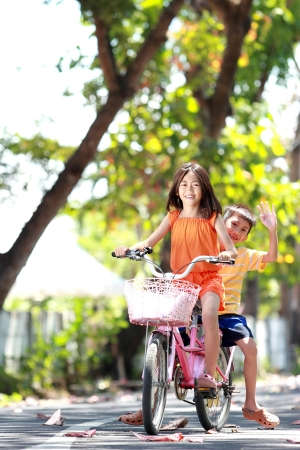 asian family fun: happy smiling kids enjoy riding bicycle together outdoor
