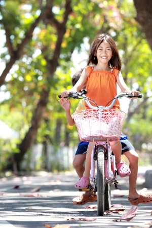bicycle girl: happy smiling little girl and boy enjoy riding bicycle together outdoor
