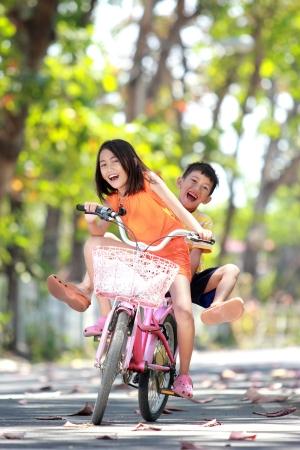 hermanos jugando: feliz niña sonriente y niño montando bicicleta junto al aire libre Foto de archivo