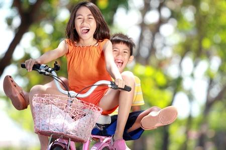 hermanos jugando: felices los niños sonrientes disfrutar de paseos en bicicleta junto al aire libre Foto de archivo