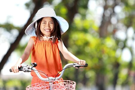 street kid: portrait of smiling litte girl riding bicycle outdoor
