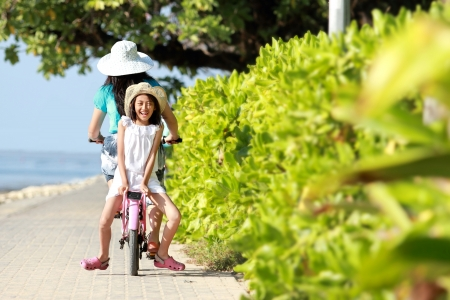 young little girl having fun with bicycle outdoor photo