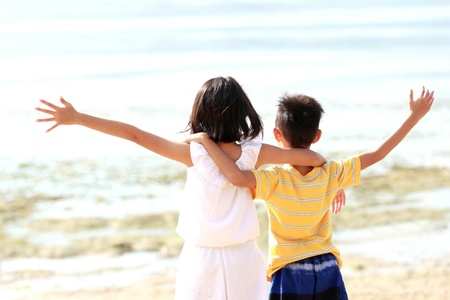 to raise: Cute little girl and boy raises their hands against blue sky