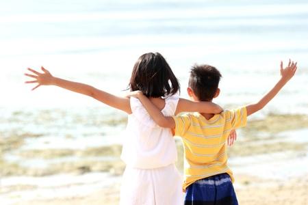 raise hand: Cute little girl and boy raises their hands against blue sky