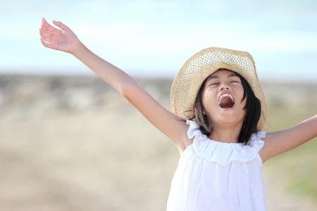 Cute little girl raises her hands against blue sky photo