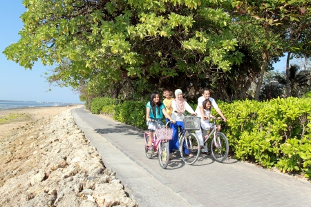 happy asian family riding bicycle outdoor in the morning photo