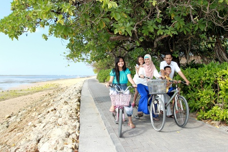 kids having fun: family with kids enjoy riding bicycle outdoor in the beach