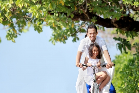 healthy asian family: father and daughter riding bikes together