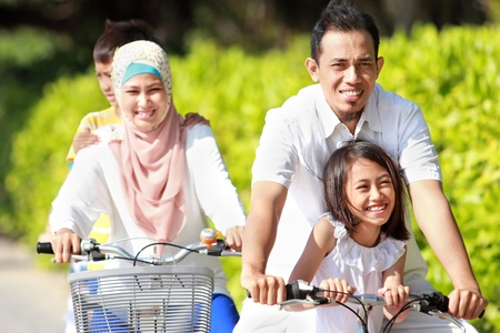 muslim: Happy asian family riding bikes in the beautiful morning