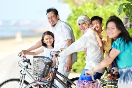 asian sport: Happy asian family riding bikes in the beautiful morning at the beach