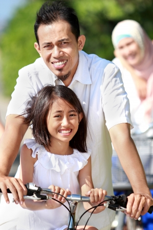portrait of Happy asian family riding bikes outdoor photo