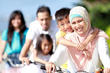 mujeres musulmanas: Familia feliz asi�tica andar en bicicleta por la ma�ana al aire libre hermoso Foto de archivo