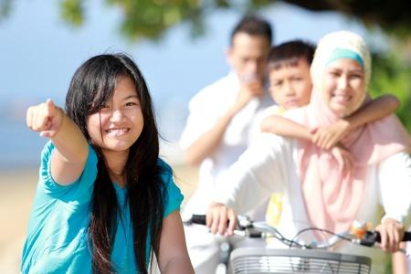 scarf beach: chica joven con su familia a andar en bicicleta al aire libre
