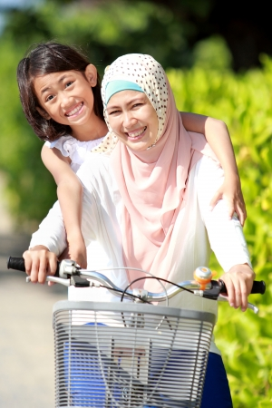 moslem: smiling happy mother with her daughter riding bicycle Stock Photo