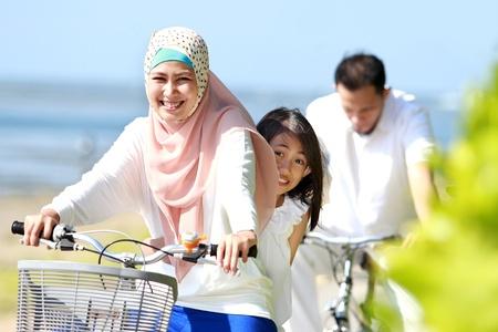 femmes muslim: m�re avec sa fille faire du v�lo dans la belle matin�e � la plage