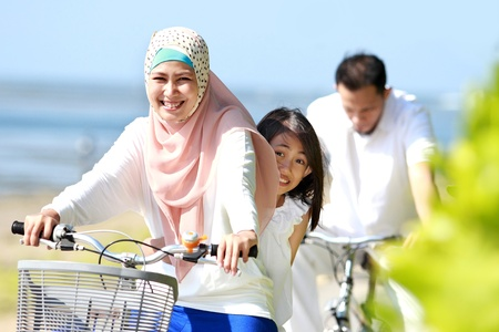 asian family fun: mother with her daughter riding bikes in the beautiful morning at the beach