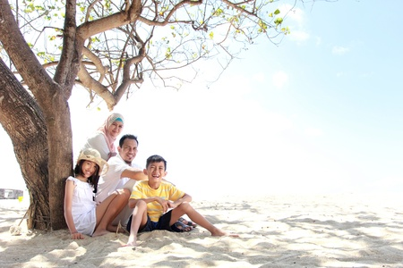 muslim woman: smiling happy family relaxing at the beach