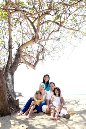 smiling happy asian family at the beach together photo