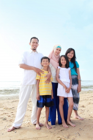 Portrait of Happy muslim Family In the beach photo