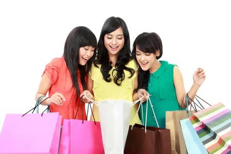 asian girl shopping: Portrait of happy shopping woman looking inside shopping bags