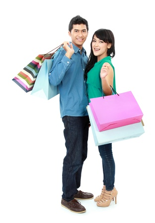 man and woman with shopping bags: Romantic young couple shopping and holding many shopping bags isolated on white background