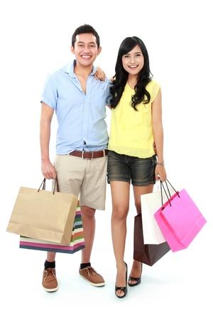 chicas comprando: Joven pareja rom�ntica con bolsas de compras y muchas compras aislados sobre fondo blanco