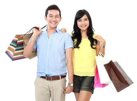 asian girl shopping: Romantic young couple shopping and holding many shopping bags isolated on white background