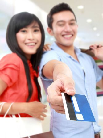 Romantic young couple shopping at the mall and paying using credit card photo