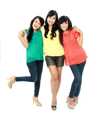 Portrait of attractive three teenage girls hugging each other isolated on white background photo