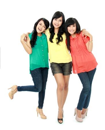 Ritratto di tre ragazze adolescenti attraenti abbracciano isolato su sfondo bianco